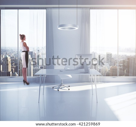 Businesswoman looking outside of window in bright office interior with workplace and New York city view. 3D Rendering - stock photo