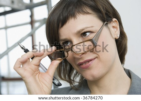Businesswoman looking over eyeglasses with questions - stock photo