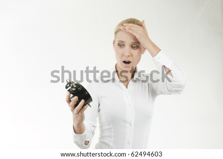 Businesswoman looking shocked at the clock - stock photo