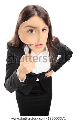 Businesswoman looking through a magnifying glass isolated on white background - stock photo