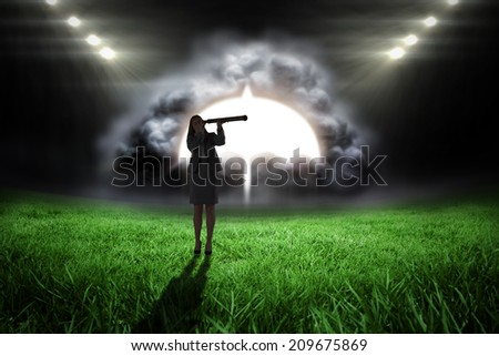Businesswoman looking through a telescope against football pitch with bright lights