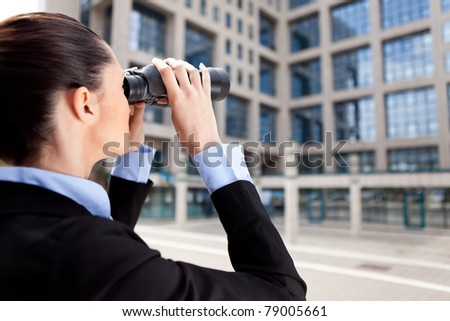 businesswoman looking through binoculars in competition building - stock photo