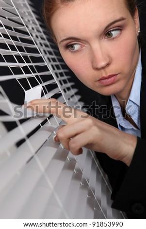 businesswoman looking through the blinds - stock photo