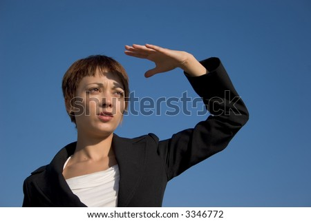 Businesswoman looking with far the hand on the face - stock photo