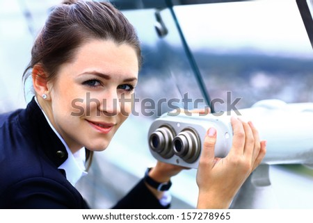 Businesswoman looks through telescope on the city building - stock photo