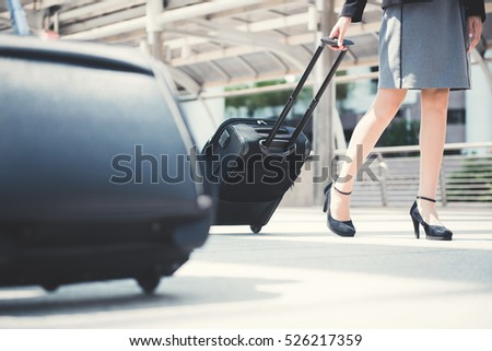 Businesswoman (lower part) walking and pulling luggage - business traveling concept