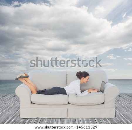Businesswoman lying on couch and using her laptop