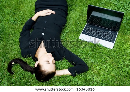 Businesswoman lying on grass with laptop - stock photo