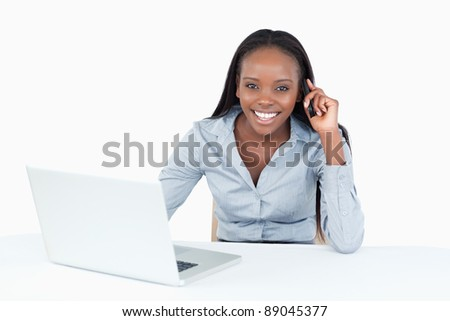 Businesswoman making a phone call while using a laptop against a white background - stock photo