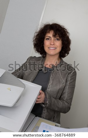 Businesswoman making copies on the photocopy machine at the office - stock photo
