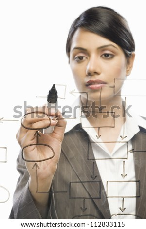 Businesswoman making flow chart on a glass against a white background - stock photo