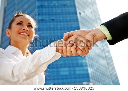Businesswoman making handshake with partner over office building - stock photo