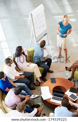 Businesswoman Making Presentation To Office Colleagues - stock photo