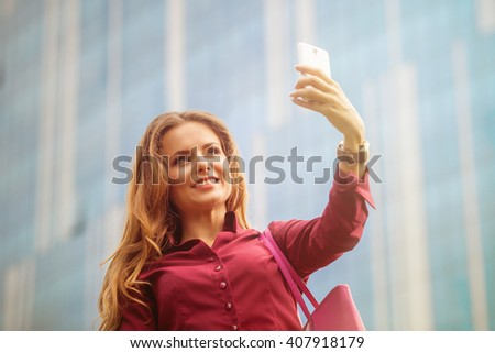 Businesswoman making selfies in front of office building. Smiling lady taking photos for her business partners abroad.  - stock photo