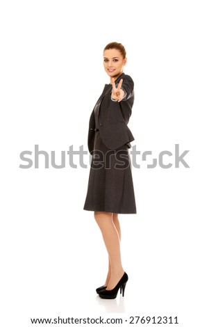 Businesswoman making victory gesture with hand. - stock photo