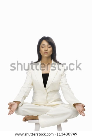 Businesswoman meditating on a stool - stock photo