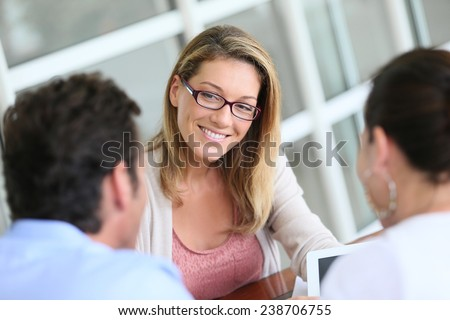 Businesswoman meeting with couple to sign financial contract - stock photo