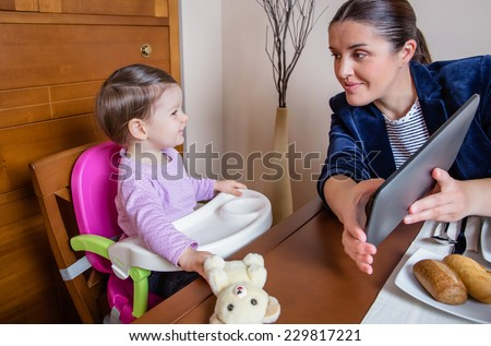 Businesswoman mother and happy baby girl looking tablet computer sitting in a restaurant table - stock photo