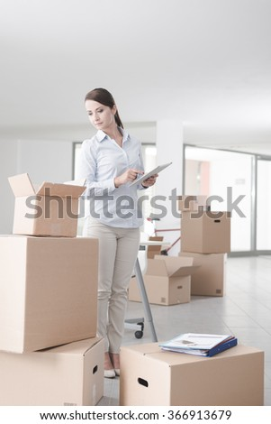Businesswoman moving in her new office surrounded by cardboard boxes, she is holding a digital tablet - stock photo