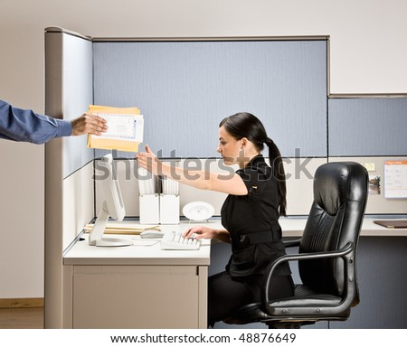 Businesswoman multi-tasking at desk in cubicle - stock photo