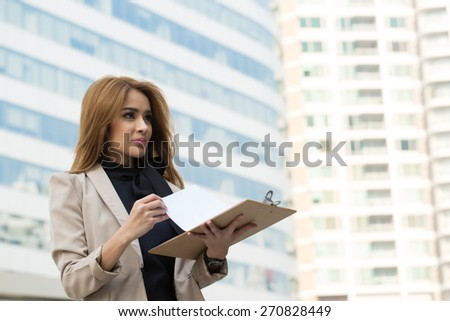Businesswoman note and think her job with wood board. - stock photo