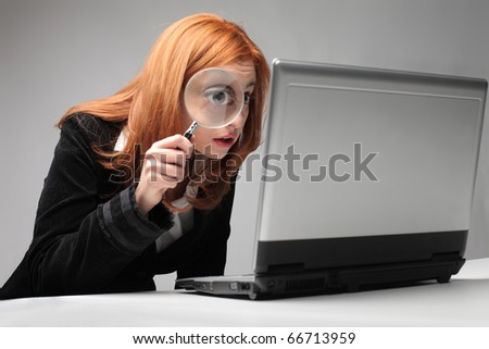 Businesswoman observing a laptop with a magnifying glass - stock photo