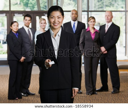 Businesswoman offering business card in front of co-workers - stock photo