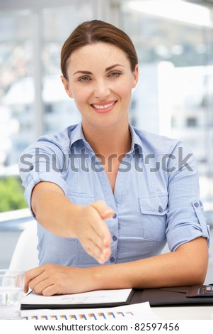 Businesswoman offering hand in greeting - stock photo