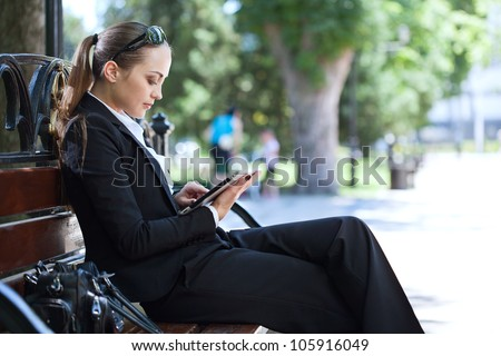 businesswoman on bench in park - stock photo