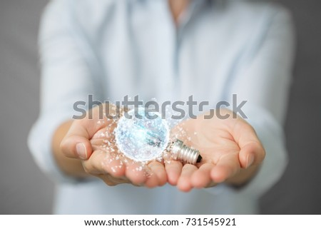 Businesswoman on blurred background holding a lighbulb with connections in her hand