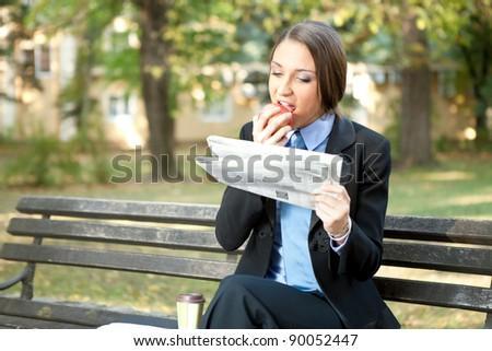 businesswoman on break eating apple and reading newspaper - stock photo
