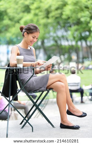 Businesswoman on break in park. Young professional business woman using tablet computer in Bryant Park, New York City, USA. Mixed race Asian Chinese / Caucasian female model. - stock photo