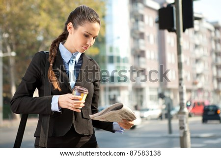 businesswoman  on her way to work reading the newspaper - stock photo