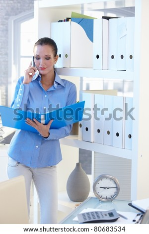 Businesswoman on mobile phone call checking documents in folder, standing at shelf.? - stock photo