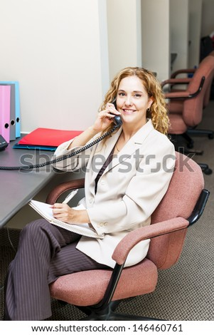 Businesswoman on phone taking notes in office workstation - stock photo