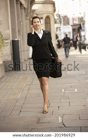 Businesswoman on phone walking down street - stock photo