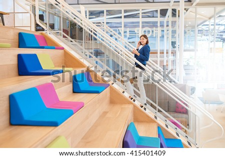 Businesswoman on phone walking up stairs with takeaway coffee - stock photo