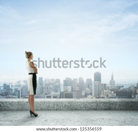 businesswoman on roof looking at city - stock photo
