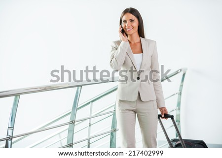 Businesswoman on the go. Beautiful young businesswoman in suit talking on the mobile phone and smiling while getting out of elevator - stock photo