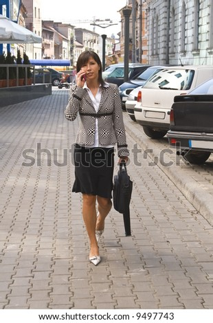 Businesswoman on the mobile phone in a city street. - stock photo