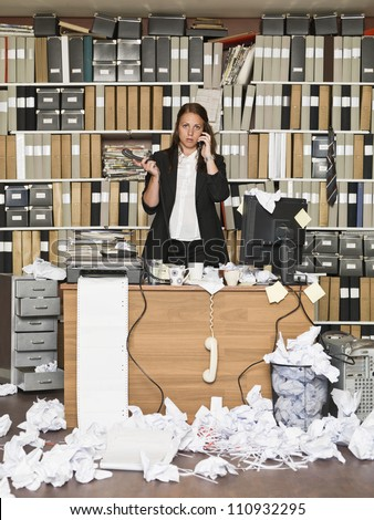 Businesswoman on the phone at the messy office - stock photo