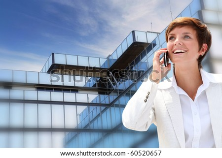 Businesswoman on the phone in front of building - stock photo