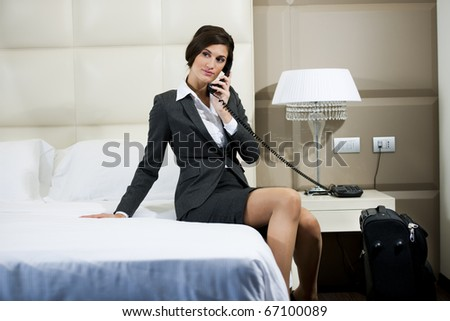 Businesswoman on the phone in hotel room - stock photo
