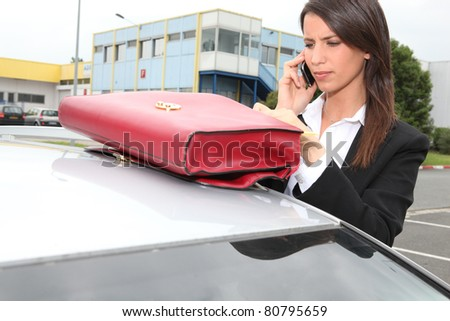 Businesswoman on the phone next to her car