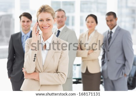 Businesswoman on the phone smiling at camera with team behind her in the office - stock photo