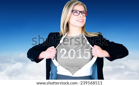 Businesswoman opening shirt in superhero style against blue sky over clouds - stock photo