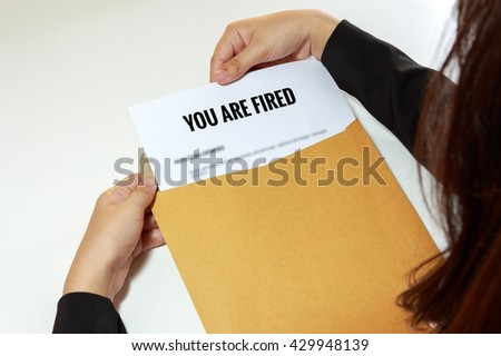 Businesswoman opening the Fired document in letter envelope.