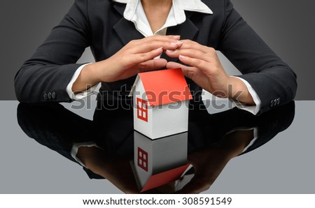 Businesswoman or estate agent and holding a model house and reflections - stock photo