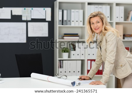 Businesswoman or female architect in her office standing at a table working on paperwork with a rolled up drawing in front of her while smiling at the camera - stock photo