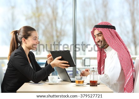 Businesswoman or saleswoman working with an arab man showing products in a tablet in a coffee shop - stock photo